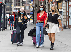 Licensed to London News Pictures. 12/07/2021. London, UK. Train travellers wear masks in Victoria, London ahead of the Prime Minister's speech on unlocking of restricts later today. Boris Johnson will hold a TV press conference today on the government's decision to go ahead with unlocking England from Covid-19 restrictions on 19 July 2021 with the possible dropping of rules on face masks, gatherings, social distance and work from home rules. Photo credit: Alex Lentati/LNP
