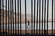 A Mexican man walks on the Mexico side of the border fence..The rusty border fence that separates the U.S and Mexico extends briefly in to the Pacific Ocean. The once porous beach border area is now highly patrolled by U.S. Border Patrol, with very few Mexican immigrants making their passage in to the U.S..