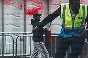 """A member of the G4S private security firm reacts as he fleed the scene as an activist from the Palestine Action activist group is seen using an extinguisher with red paint spraying their security tent outside Abu Dhabi National Exhibition Centre Excel in East London on Sunday, Sept 12, 2021. Activists are targeting an arms fair hailed as """"the world's largest gathering of the defence and security community"""". (VX Photo/ Vudi Xhymshiti)"""