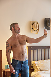shirtless man taking a selfie in a bedroom