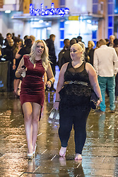 """© Licensed to London News Pictures . 15/12/2012 . Manchester , UK . A woman removes her shoes and walks barefoot on the wet street . Revellers enjoy a wet but busy night out on one of the last weekends before Christmas , a traditionally busy time when office parties and clubbers decent on bars and clubs , often known as """" Mad Friday """" . Photo credit : Joel Goodman/LNP"""