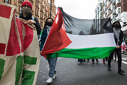 Protesters hold a Palestinian flag during a Free Palestine SOS Colombia march in solidarity with the Palestinian and Colombian peoples from the Colombian embassy to the Israeli embassy on 15th May 2021 in London, United Kingdom. Speakers at a rally before the march, which took place on Nakba Day, highlighted human rights abuses being directed against Palestinians in Israel and the Occupied Territories, in particular attempts at forced displacements in Sheikh Jarrah in East Jerusalem, and also in Colombia, where peaceful demonstrators and human rights defenders have been killed and subjected to repression, detention and torture.
