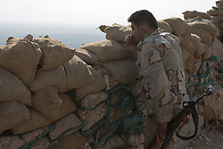 © Licensed to London News Pictures. 01/09/2015. Bashiqa, Iraq. A Kurdish peshmerga fighter keeps watch from a position on top of Bashiqa Mountain near Mosul, Iraq.<br /> <br /> Bashiqa Mountain, towering over the town of the same name, is now a heavily fortified front line. Kurdish peshmerga, having withdrawn to the mountain after the August 2014 ISIS offensive, now watch over Islamic State held territory from their sandbagged high-ground positions. Regular exchanges of fire take place between the Kurds and the Islamic militants with the occupied Iraqi city of Mosul forming the backdrop.<br /> <br /> The town of Bashiqa, a formerly mixed town that had a population of Yazidi, Kurd, Arab and Shabak, now lies empty apart from insurgents. Along with several other urban sprawls the town forms one of the gateways to Iraq's second largest city that will need to be dealt with should the Kurds be called to advance on Mosul. Photo credit: Matt Cetti-Roberts/LNP