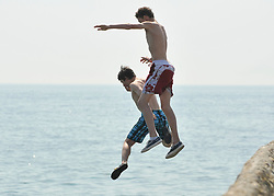 © licensed to London News Pictures. BRIGHTON  UK. 21/04/11.Two young boys jump into the sea. People flock to Brighton Beach today to catch the sunshine before the start of the Easter Bank Holiday in Britain. Temperatures are set to continue to rise over the weekend. Photo credit should read Stephen Simpson/LNP