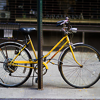 Antique looking bike locked to a street sign in New York city