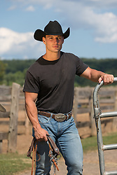 handsome cowboy in a black tee shirt on a ranch