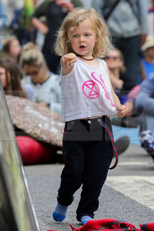 © Licensed to London News Pictures. 15/07/2019. London, UK. 4 years old Cassidy joins hundreds of Extinction Rebellion climate change activists protesters outside the Royal Courts of Justice demanding the legal system take responsibility in the climate change crisis, and ensure the safety of future generations by making ecocide law. The environmental group is staging similar protests in Leeds, Cardiff, Glasgow, Bristol, Norwich and other cities around the country. <br /> <br /> **Permission granted by the parent***.<br /> <br /> Photo credit: Dinendra Haria/LNP