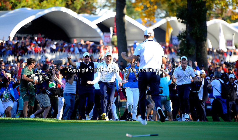 Martin KAYMER (GER) secures point for Europe to retain Ryder Cup at 18th V Steve STRICKER (US) during final day Singles,Ryder Cup Matches,Medinah CC,<br /> Medinah,Illinois,USA.With P Hanson,Sergio Garcia and Rory MCILROY his EUR team mates looking on in triumph.