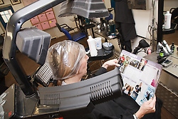 Woman at hairdresser's reads a magazine