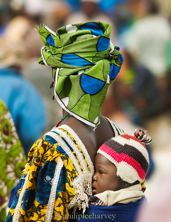 A woman with child on her back walks around the weekly market in Djenné, Mali