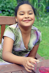 Portrait of young girl sitting at picnic table smiling,