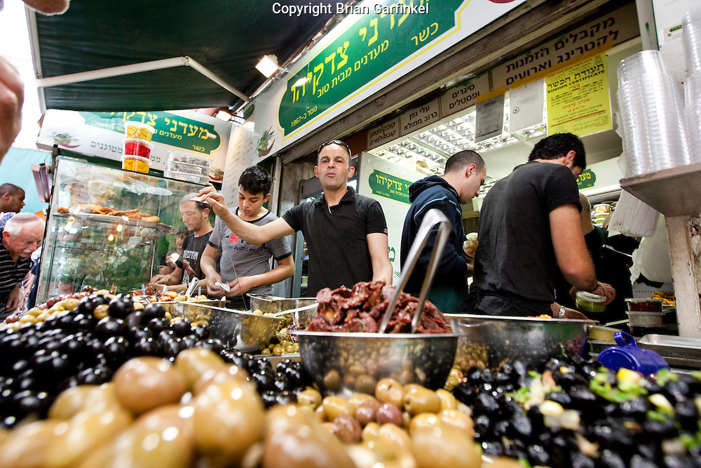 Day 4 -  A shop keeper sells olives in a market in Jerusalem (Photo by Brian Garfinkel)