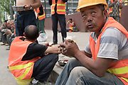 Workers take a break for lunch from the building work<br /><br />Huge construction and recently built tower blocks in Tongzhou city on the outskirts of Beijing. All the old buildings, villages have been destroyed to make way for the mega cities of today