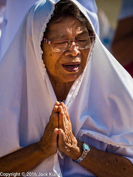 """02 JANUARY 2016 - KHLONG LUANG, PATHUM THANI, THAILAND: A woman prays at Wat Phra Dhammakaya on the first day of the 5th annual Dhammachai Dhutanaga (a dhutanga is a """"wandering"""" and translated as pilgrimage). More than 1,300 monks are participating pilgrimage through central Thailand. The purpose of the pilgrimage is to pay homage to the Buddha, preserve Buddhist culture, welcome the new year, and """"develop virtuous Buddhist youth leaders."""" Wat Phra Dhammakaya is the largest Buddhist temple in Thailand and the center of the Dhammakaya movement, a Buddhist sect founded in the 1970s. The monks are using busses on some parts of the pilgrimage this year after complaints about traffic jams caused by the monks walking along main highways.          PHOTO BY JACK KURTZ"""