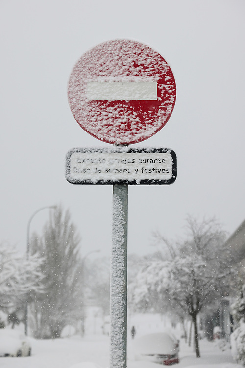 MADRID, SPAIN - JANUARY 9: A stop traffic sign almost covered in snow stand at an intersection of streets in a residential area as storm Filomena hits the area on January 9, 2021, in Majadahonda, Madrid, Spain.