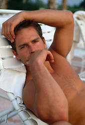 Shirtless  man sitting on a lounge chair looking pensive and thoughtful