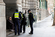 A man without a facemask is seen being questioned by a group of police during COVID-19 in Melbourne, Australia. Victoria has recorded 14 COVID related deaths including a 20 year old, marking the youngest to die from Coronavirus in Australia, and an additional 372 new cases overnight. (Photo by Dave Hewison/Speed Media)