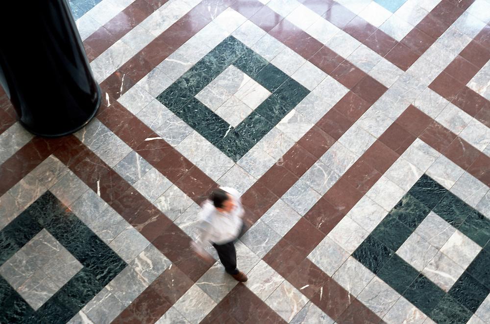 male figure walking on marble tiles