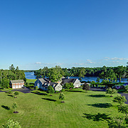 This real estate marketing image shows an overview of the Three Rivers Farm property in Dover, NH. From a vantage point about 60 feet up, it captures the main buildings, extensive grounds, and river setting, all in a single shot that would be impossible from the ground, and very challenging with traditional aerial techniques due to surrounding obstructions.