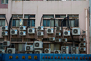 Wall mounted air conditioning units behind a building in Hong Kong.