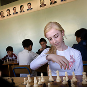 Aline Kuzichenko, 13, attends compulsory chess class in Elista, capital of the southern Russian republic of Kalmykia...The province is run by President Kirsan Ilyumzhinov, 44, who is a millionaire businessman and chess fanatic. He made chess compulsory in all schools. ..Ilyumzhinov, also the president of Fide, the World Chess Federation, is hosting the world?s most important match in September 2006. ..The match, beginning September 21 in Elista, will end a 13-year split in the game that has produced rival claims to the title. ..Veselin Topalov, a Bulgarian ranked first according to Fide, will play against Vladimir Kramnik, who is the Classical Chess World Champion, a title established after Garry Kasparov led a breakaway from Fide in 1993. The two grandmasters, both aged 31, will face each other for the right to be undisputed world chess champion...Ilyumzhinov acquired his wealth in the economic free-for-all which followed the collapse of the Soviet Union. ..At the age of just over 30, he was elected president in 1993 after promising voters $100 each and a mobile phone for every shepherd. Soon after, he introduced presidential rule, concentrating power in his own hands. ..He denies persistent accusations of corruption, human rights abuses and the suppression of media freedom. When Larisa Yudina, editor of the republic's only opposition newspaper and one of his harshest critics, was murdered in 1998, he strenuously rejected allegations of involvement. ..Mr Ilyumzhinov has been president of the International Chess Federation (FIDE) since 1995 and has been enthusiastic about attracting international tournaments to Kalmykia. His extravagant Chess City has led to protests by its impoverished citizens..