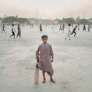 A boy plays cricket in 40 degrees heat.