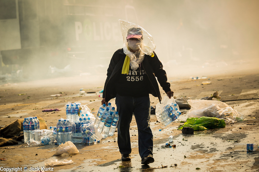 02 DECEMBER 2013 - BANGKOK, THAILAND: An anti-government protestor carries cases of water through a cloud of tear gas in Bangkok. The protestors use the water to rinse tear gas out of their eyes. Anti-government protestors and Thai police continued to face off Monday for a second day. Police used tear gas, water cannons and rubber bullets against protestors who charged their positions near the barriers on Chamai Maruchet bridge on Phitsanulok Road, which leads to the Government House.     PHOTO BY JACK KURTZ