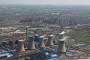 A view of a coal burning power plant operating near a large new housing development seen from an airplane near Tianjin, China on 16 July 2013. Despite continued government efforts to cool the property market, housing prices across China continue to grow rapidly.
