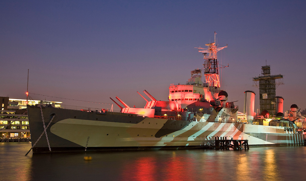 HMS belfast at night with coloured lighting and blue sky