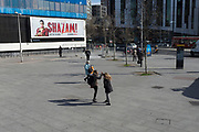 Two young women high-five each other at Elephant & Castle in Southwark, on 25th March 2019, in London, England.