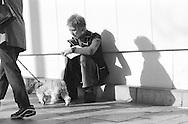 1999, MARCH - A man sits on the sidewalk on Omotesando, near Meiji Shrine in Harajuku, Tokyo, Japan. By Richard Walker
