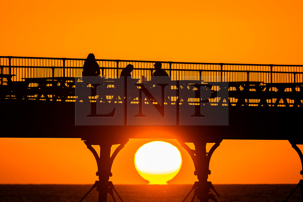 ©Licensed to London News Pictures. 17/09/2019 Aberystwyth UK. <br /> People having a drink on Aberystwyth's Victorian seaside pier are silhouetted as they watch the last  of the sun as it sets over Cardigan Bay, framed by the cast iron legs , on a glorious early autumn evening. Photo credit Keith Morris/LNP