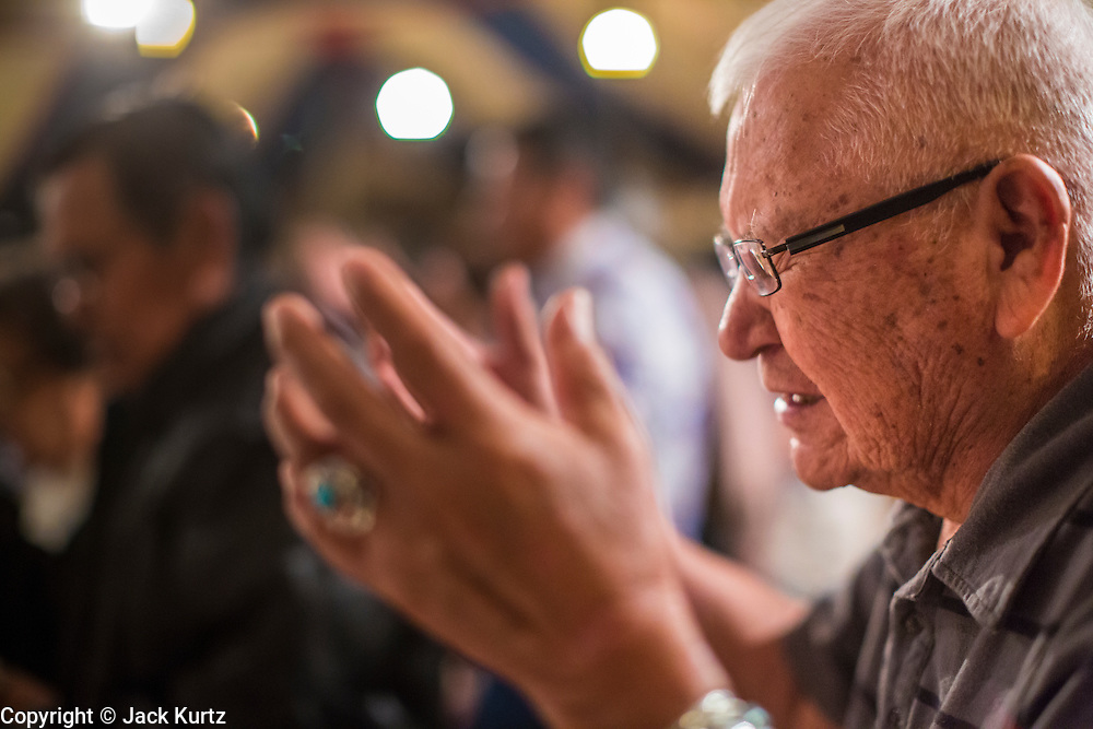 """12 JULY 2012 - FT DEFIANCE, AZ: A man prays during alter call at the 23rd annual Navajo Nation Camp Meeting in Ft. Defiance, north of Window Rock, AZ, on the Navajo reservation. Preachers from across the Navajo Nation, and the western US, come to Navajo Nation Camp Meeting to preach an evangelical form of Christianity. Evangelical Christians make up a growing part of the reservation - there are now more than a hundred camp meetings and tent revivals on the reservation every year. The camp meeting in Ft. Defiance draws nearly 200 people each night of its six day run. Many of the attendees convert to evangelical Christianity from traditional Navajo beliefs, Catholicism or Mormonism. """"Camp meetings"""" are a form of Protestant Christian religious services originating in Britain and once common in rural parts of the United States. People would travel a great distance to a particular site to camp out, listen to itinerant preachers, and pray. This suited the rural life, before cars and highways were common, because rural areas often lacked traditional churches.   PHOTO BY JACK KURTZ"""