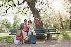 Two mature women on park bench with shopping bags, Bavaria, Germany
