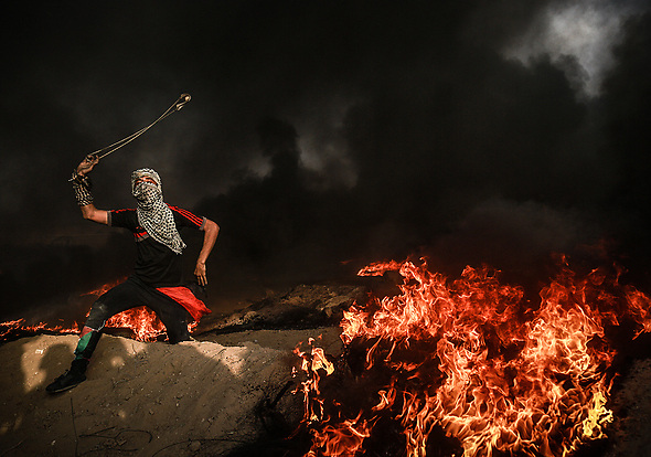 October 19, 2018 - Gaza Strip - A Palestinian protester seen throwing a stone towards the Israeli forces during the clashes between Palestinians and Israel at the Gaza Strip's border. (Credit Image: © Nidal Alwaheidi/SOPA Images via ZUMA Wire)