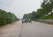 HIGHWAY TO YELL IN NORTH KOREA<br /><br />Taking the highways in North Korea is a great experience as it allows to see the daily life of the country not controled by the government like in Pyongyang. They connect the main towns of the countries and are totally empty of cars. It makes a very strange atmosphere as the roads are as large as airstrips, but in bad shapes with lot of bumpings and holes.<br />Everything is planned when you travel in North Korea, even the bathrooms stops, as according to the guide, it is too dangerous to stop on the highway to make a pee stop!<br />Some shops in the middle of nowhere welcome you for a relaxing moment where one more time, you'll be able to read some propaganda on the walls. It will also allow your driver to buy cheap Soju (rice alcool) that they drink like Red Bulls but with different side effects!<br /><br />Photo Shows:  Lot of holes can be found on the highways, so lot of workers try to fix the road. Security is not the main concern, the sign is just in front of the workers, not 200m before!<br />©Eric Lafforgue/Exclusivepix Media