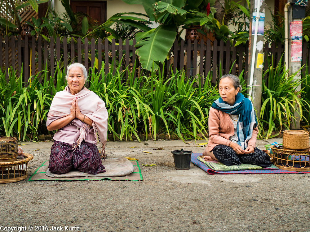"""11 MARCH 2016 - LUANG PRABANG, LAOS:  Lao women wait for Buddhist monks to pass him during the morning tak bat in Luang Prabang. Luang Prabang was named a UNESCO World Heritage Site in 1995. The move saved the city's colonial architecture but the explosion of mass tourism has taken a toll on the city's soul. According to one recent study, a small plot of land that sold for $8,000 three years ago now goes for $120,000. Many longtime residents are selling their homes and moving to small developments around the city. The old homes are then converted to guesthouses, restaurants and spas. The city is famous for the morning """"tak bat,"""" or monks' morning alms rounds. Every morning hundreds of Buddhist monks come out before dawn and walk in a silent procession through the city accepting alms from residents. Now, most of the people presenting alms to the monks are tourists, since so many Lao people have moved outside of the city center. About 50,000 people are thought to live in the Luang Prabang area, the city received more than 530,000 tourists in 2014.      PHOTO BY JACK KURTZ"""