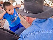 """13 JULY 2012 - FT DEFIANCE, AZ: A Navajo boy talks to a horse wrangler during the horsemanship clinic  at the 23rd annual Navajo Nation Camp Meeting in Ft. Defiance, north of Window Rock, AZ, on the Navajo reservation. Preachers from across the Navajo Nation, and the western US, come to Navajo Nation Camp Meeting to preach an evangelical form of Christianity. Evangelical Christians make up a growing part of the reservation - there are now more than a hundred camp meetings and tent revivals on the reservation every year. The camp meeting in Ft. Defiance draws nearly 200 people each night of its six day run. Many of the attendees convert to evangelical Christianity from traditional Navajo beliefs, Catholicism or Mormonism. """"Camp meetings"""" are a form of Protestant Christian religious services originating in Britain and once common in rural parts of the United States. People would travel a great distance to a particular site to camp out, listen to itinerant preachers, and pray. This suited the rural life, before cars and highways were common, because rural areas often lacked traditional churches. PHOTO BY JACK KURTZ"""