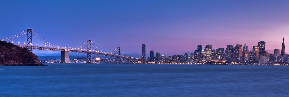 san francisco city skyline and the bay bridge at dusk from treasure island, panoramic shot.
