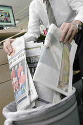 Office worker putting newspapers in rubbish bin UK