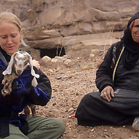 A traveler admires a Bedouin woman's baby goat near Petra, Jordan.