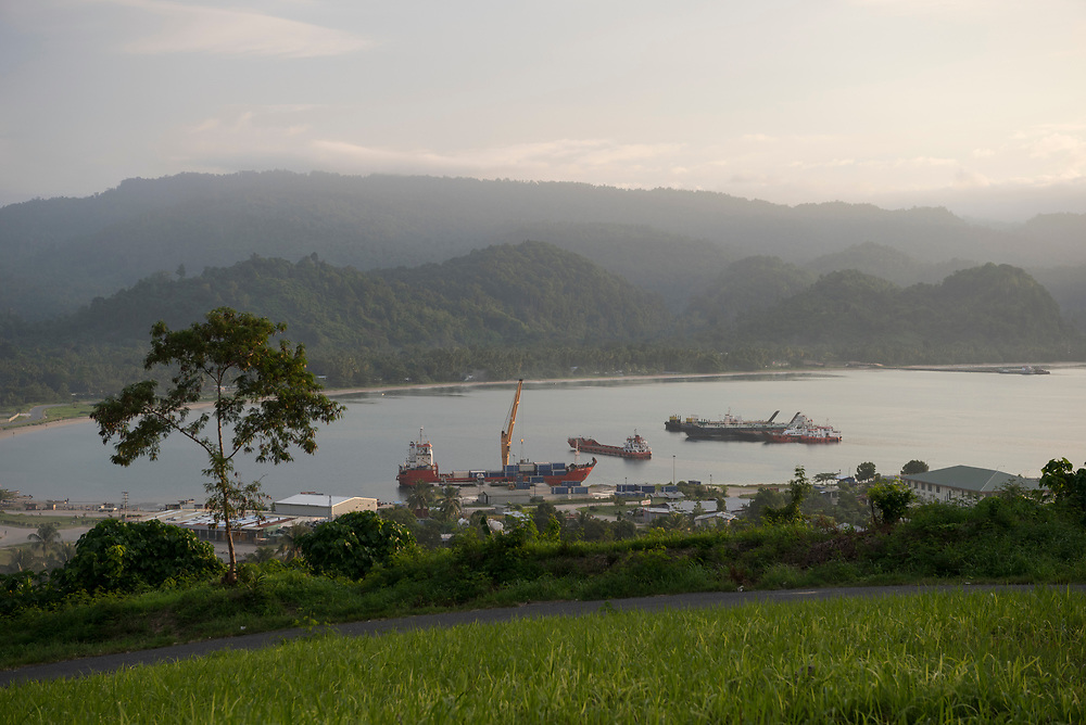 A small container ship is docked in the port town of Vanimo, Papua New Guinea. Photo taken at sunset. (2017)