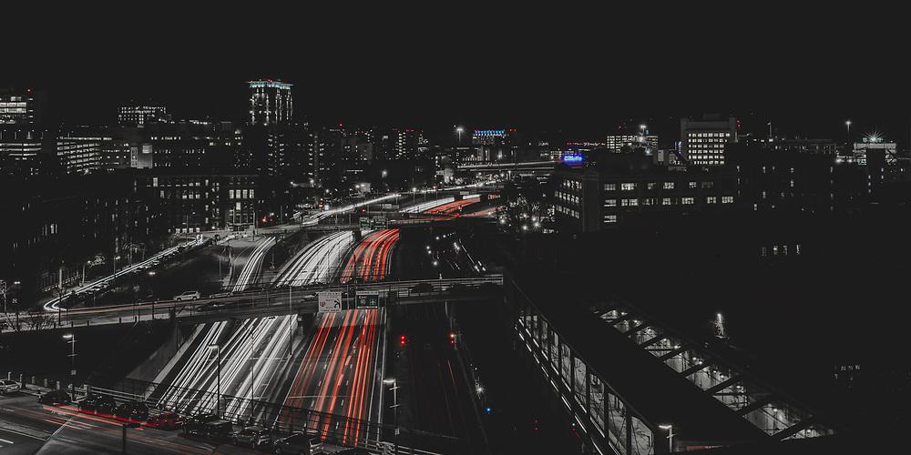 Mass Pike traffic rolls through the Boston skyline on a cold winter night.