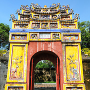 A brighly colored courtyard gate at the Imperial City in Hue, Vietnam. A self-enclosed and fortified palace, the complex includes the Purple Forbidden City, which was the inner sanctum of the imperial household, as well as temples, courtyards, gardens, and other buildings. Much of the Imperial City was damaged or destroyed during the Vietnam War. It is now designated as a UNESCO World Heritage site.