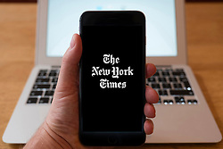 Using iPhone smartphone to display logo of The New York Times newspaper