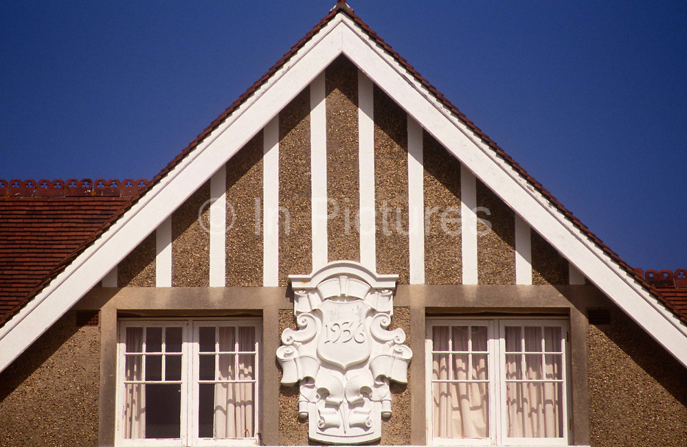 A detail of a 1930s house gable in the Essex seaside town of Frinton-on-Sea. Well-painted white woodwork looks fresh and clean despite it being 90 years old. The property is shown as Essex House with the date of its construction as 1936. A gable is the generally triangular portion of a wall between the edges of a sloping roof. The shape of the gable and how it is detailed depends on the structural system used (which is often related to climate and availability of materials) and aesthetic concerns. Thus the type of roof enclosing the volume dictates the shape of the gable. A gable wall or gable end more commonly refers to the entire wall, including the gable and the wall below it.