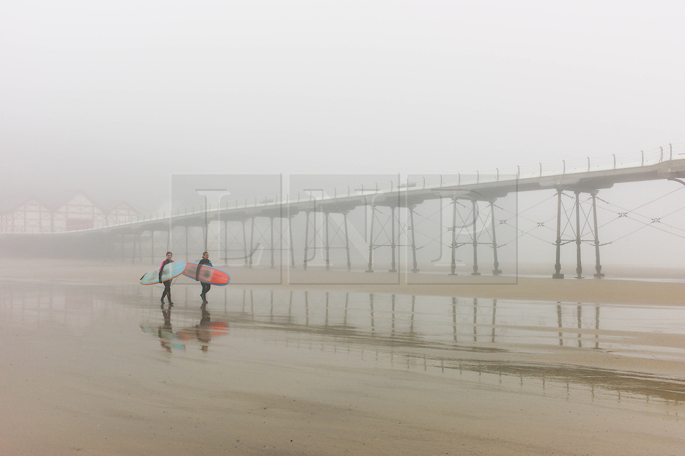 © Licensed to London News Pictures. <br /> 08/05/2016. <br /> Saltburn by the Sea, UK.  <br /> <br /> Two surfers walk alongside the fog shrouded pier as heavy fog shrouds the coastline at Saltburn by the Sea in North Yorkshire as much of the country enjoys the hottest temperatures of the year so far.<br /> <br /> Photo credit: Ian Forsyth/LNP