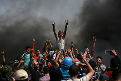 April 13, 2018 -  Gaza, Gaza Strip - Palestinian protesters take part in clashes with Israeli troops on the Gaza-Israel border, east of Gaza City. At least 30 Palestinians were injured in clashes Friday between demonstrators and Israeli soldiers in eastern Gaza Strip. (Credit Image: © Stringer/Xinhua via ZUMA Wire)