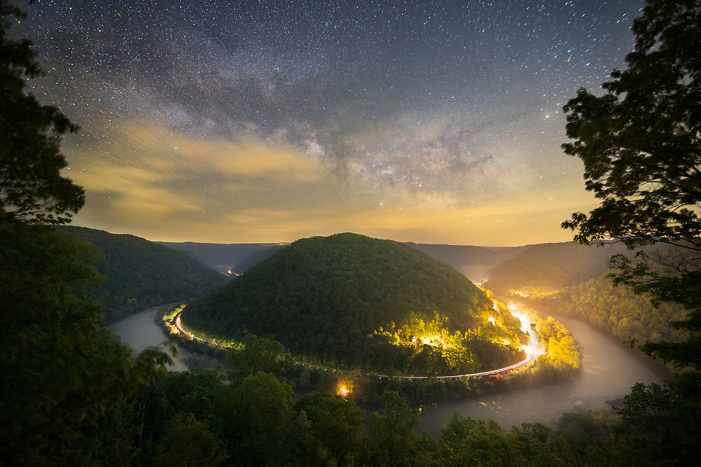On an early Spring night the Milky Way can be seen rising above the mountains of the New River Gorge in West Virginia and over the small town of Thurmond.