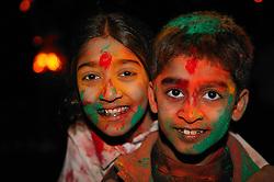Young girl and boy enjoying the Hindu Holi festival; celebration of colours,